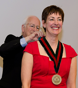 Dean Larry J. Shapiro, MD, awards a medallion to Laura Jean Bierut, MD, signifying her installation as the new Alumni Endowed Professor of Psychiatry.