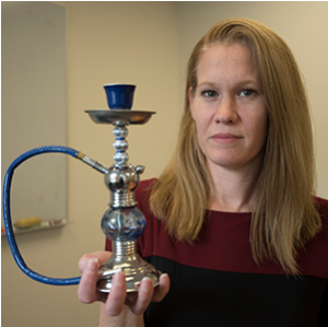 Melissa J. Krauss, a research statistician in Washington University's Department of Psychiatry, holds a hookah pipe. She found that positive mentions about hookah smoking on Twitter may promote the assumption that it is less harmful than smoking cigarettes, when hookah smoking has many of the same harmful toxins as cigarettes.