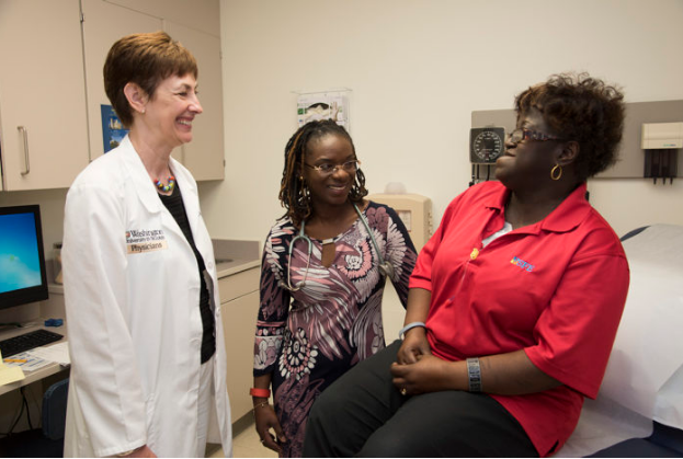 Washington University School of Medicine's Laura Jean Bierut, MD (left), and Foluso Ademuyiwa, MD (center), discuss genetic risks for breast cancer with patient Delores Ford-Dixon. Bierut and Ademuyiwa are launching a study in African-American women with breast cancer to learn whether their genetic risks are influenced by the same mutations that affect white women or are altogether different. (Photo: Robert Boston/School of Medicine)