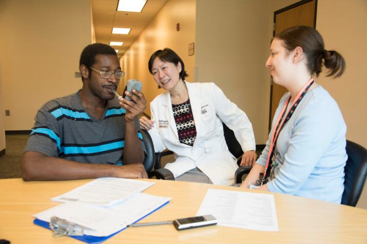 As part of a study to quit smoking, patient Antwone Daniels (left) blows into a device that measures carbon monoxide levels in his lungs. With him are researcher Li-Shiun Chen, MD (center) and health counselor Kaleigh Sills. Studying smokers, Chen and her colleagues have found that even in those at high genetic risk for heavy smoking and lung cancer, quitting can lead to big health benefits. (Photo: Robert J. Boston/School of Medicine)